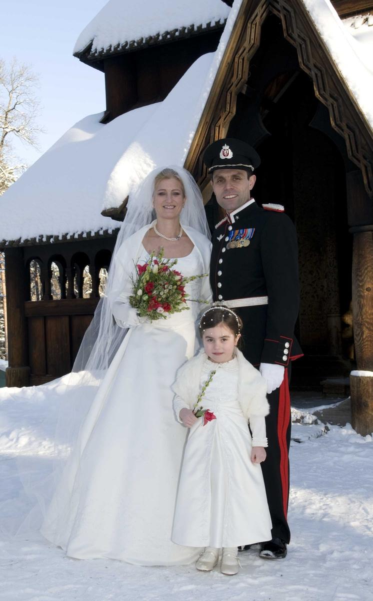 Brudepar med brudepike utenfor stavkirken.
