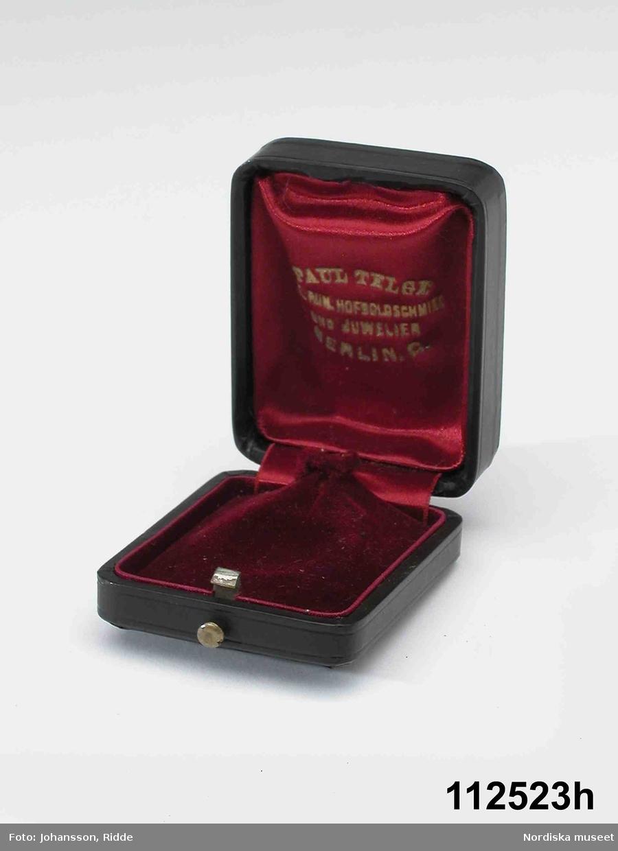 """Huvudliggaren: """"Minnen efter dr Artur Hazelius. a) Lagerkrans b1-3) Nordstjärneordens kors och kraschan i etui. c1-3)Minnespenning i etui. d1-2) Minnespenning i etui (Christ. Colombus). e) Minnespenning från utställningen i Paris 1878. f) Minnespenning i brons, amerikansk, 1887. g1-2) Kråsnål krönt E med rosenstenar och rubiner. h1-2) Belöningstecken från märk. Prov.Mus. Hazelius A., fil. dr, Stockholm. Enligt test. förordn. - Se även 121.058-121.059"""""""