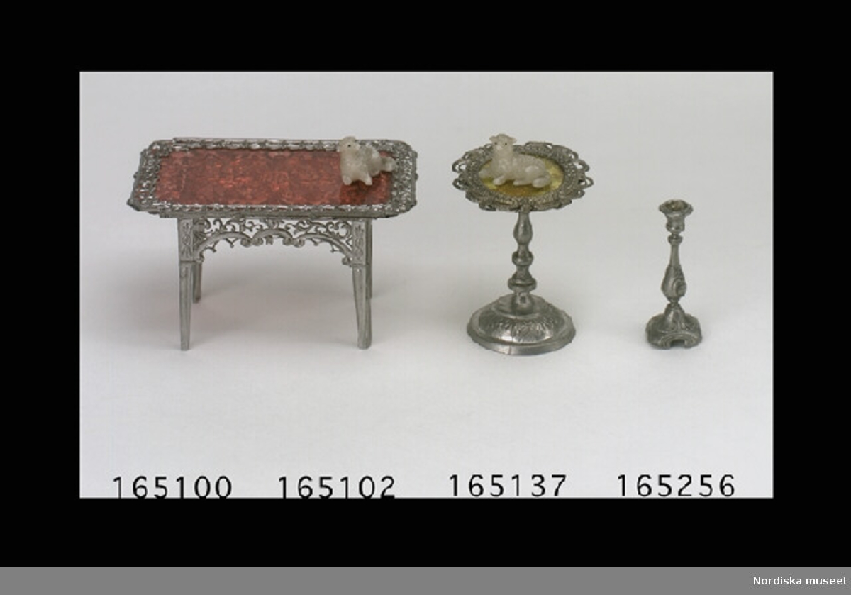 Inventering Sesam 1996-1999: L  2,5  cm 2 st lamm, prydnadsfigurer, av vax, liggande. Tillhör dockskåp inv 165.280. Bilaga Birgitta Martinius 1998