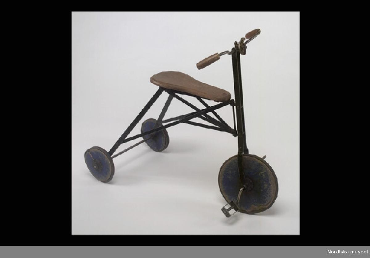 """Inventering Sesam 1996-1999: H  58   L  74   B  32 (cm) Trehjuling, leksak , stomme av järn, delvis svartlackerad, sadel och handtag av trä, skivhjul av blåmålat trä med svarta gummidäck, ringklocka av plåt, märkt: """"KRZ"""", sadeln märkt med rund, rödlackerad metallbricka: """"NK"""" (=Nordiska Kompaniet""""). Överdel till ringklocka och en trampa saknas. Bakhjulen spruckna. Har tillhört givarinnan, Kerstin Linder, f 1929, som barn. Uppvuxen på Döbelnsgatan, Stockholm, fadern jurist. Anna Womack feb 1998"""