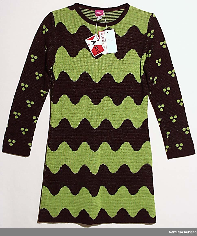 """Kortkort klänning eller tunika av grovstickad acryltrikå mönstrad med jacquardvävda tvärgående vågband i brunt och gulgrönt, ärmarna bruna med prickmönster, helskuren rak modell, 1 framstycke, 1 bakstycke, brun halskant, isydd lång ärm. Isytt firmamärke: """"Mah Jong Sweden"""" 2 hängande pappersetiketter: 1. Exlan, Acryl Turbo och tvättråd,  samt 2. Mah Jong. Fanns med i Mah Jongs första kollektion 1966. Se reportage i FORM nr 7/1966. Se även Femina nr 46/1967 och Textilbranschen nr 1/1967. Ingår i en samling representativa plagg ur Mah Jongs olika kollektioner inv.nr 313 587 - 313 630 pärmar m. skisser 313 631-632 Se även arkivet acc.nr 32/1988. Litteratur: Berit Eldvik, Mah Jong, Fataburen 1988 samt utst- katalog Hallström-Bornold: Det är rätt att göra uppror, Mah Jong 1966-1976. /Berit Eldvik 2009-08-31"""