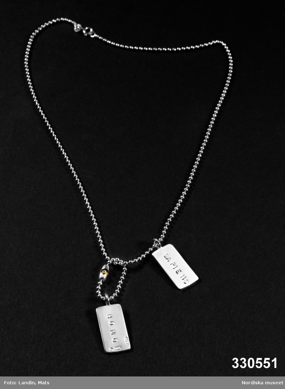 """Hängsmycke av silver bestående av två rektangulära plattor så kallade """"dog tags"""" med inskription """"HOMO"""" på en sida och """"SAPIENS"""" på andra sidan. Båda hängen likadana. Hänger på kulkedja, ena hänget med egen kort kulkedja runt den större. Stplr: """"S:t Erik  -  925  -  EFVA""""  å varje hänge. Kedjan stpl vid låset: """"ITALY   -   925"""". /Ingrid Roos 2010-11-26"""