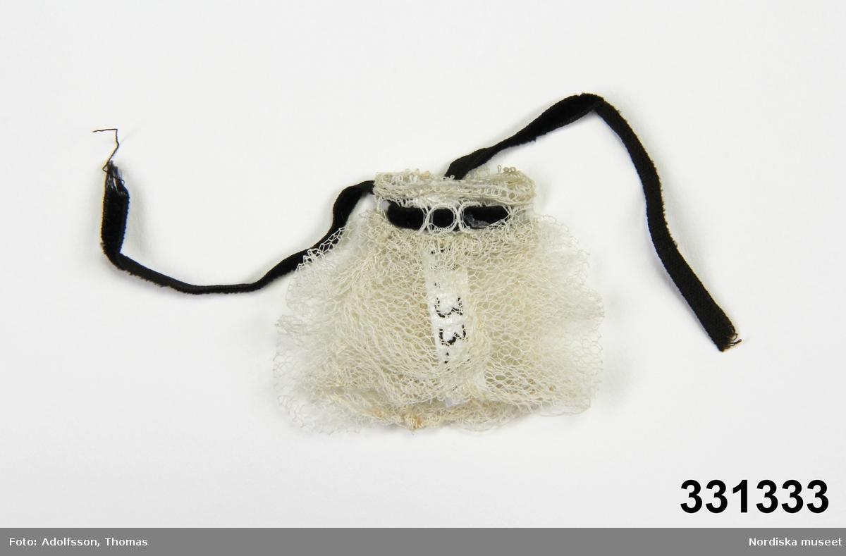 Dockmudd av vit tyll. Svart sammetsband för snörning av kanten. /Karin Dern 2011-12-16