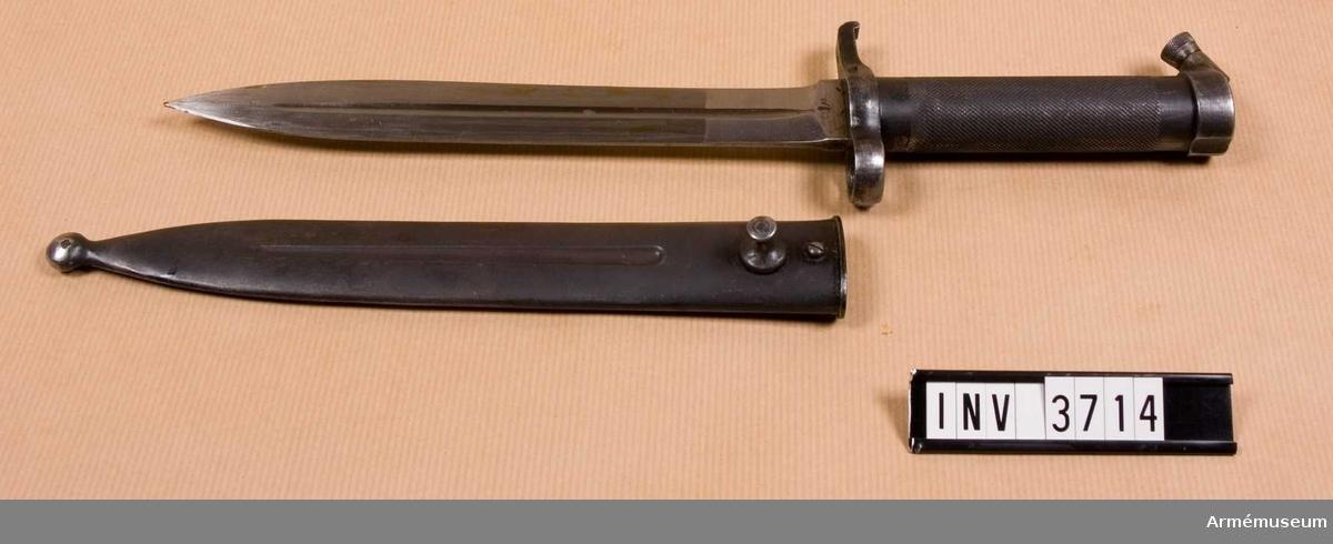 Knivbajonett m/1896 t gevär m/1896, m/1938/automatgevär m/1942.Består av: 1 bajonett, 1 balja av stål.Helt tillv. av stål med rörformigt lättrat grepp med konisk låsknapp och pipring. Rak, eneggad klinga med smal blodskåra på båda sidor. Klingb vid fästet: 25 mm. Pipringens id: 15,5 mm. Balja, l: 232 mm, vikt: 120 gr, tillv.nr 565.