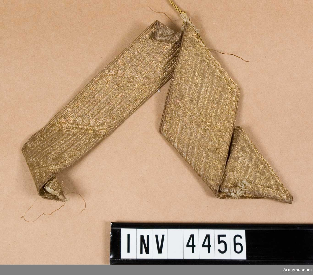 """Galon m/1939, generalsperson.Av gulddragartråd som är spunnen runt textilmaterial, förgylld efter spinning och endast å en sida. Förgyllningen skall vara 5 gr guld per kg tråd. Gjordes i två bredder: 30/40 mm. Den bredare anbringas å axelklaff och skall därvid täcka denna helt. Den smalare ingår i mössmärke t fältmössa m/1939. Galonen sys fast i en vinkel på ett underlag av tyg i samma kvalité/ färg som mössan. Märket anbringas m sin underkant i höjd m uppslagets överkant. Vidhängande etikett anger fastställelsedag: """"Stockholm Slott den 22. september 1939 Per Edvin Sköld /Henry Kellgren""""."""