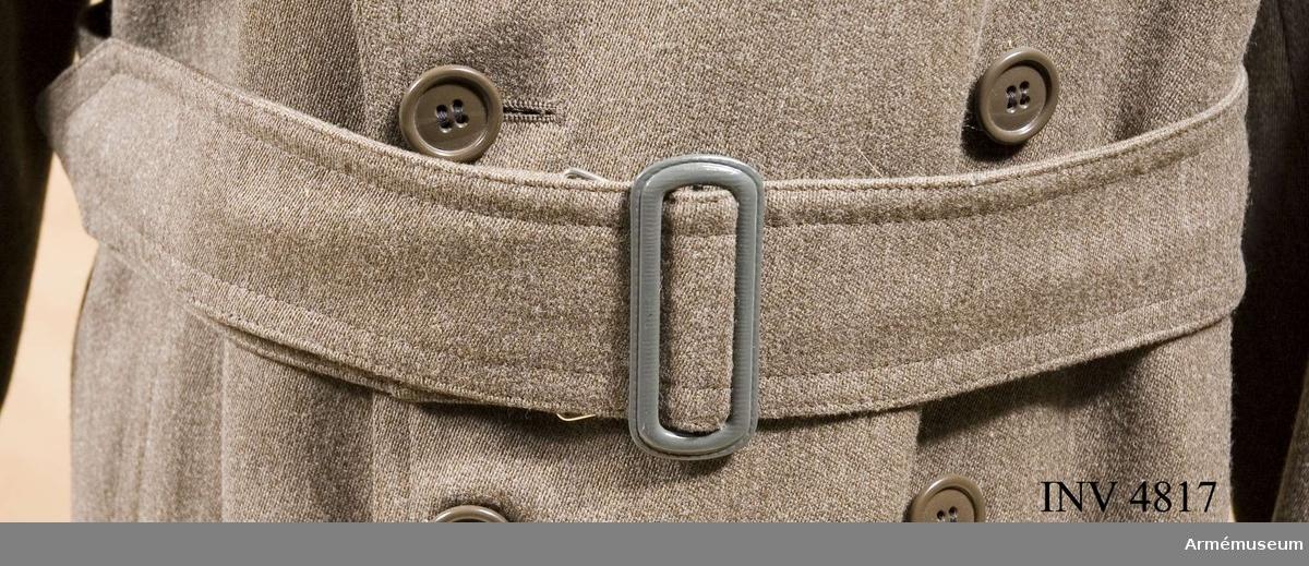 Skärp t trenchcoat, Fältläkarkår. 1923. Längd: 1200 mm. Bredd: 60 mm. Skärp till trenchcoat, tillåten modell, 1923. Av gråbrungrön  kamgarnsdiagonal, s.k. cord. På synliga sidan ett spänne i  gråmålad plåt, 70 mm högt och 30 mm brett, utan torn. På  undersidan sitter i detta spänne en stor platt hake att  fasthaka i en motsvarande hake i skärpets andra sida. Skärpet  är sytt i dubbelt tyg  och dubbelstickat i kanterna. Änden är  spetsad.
