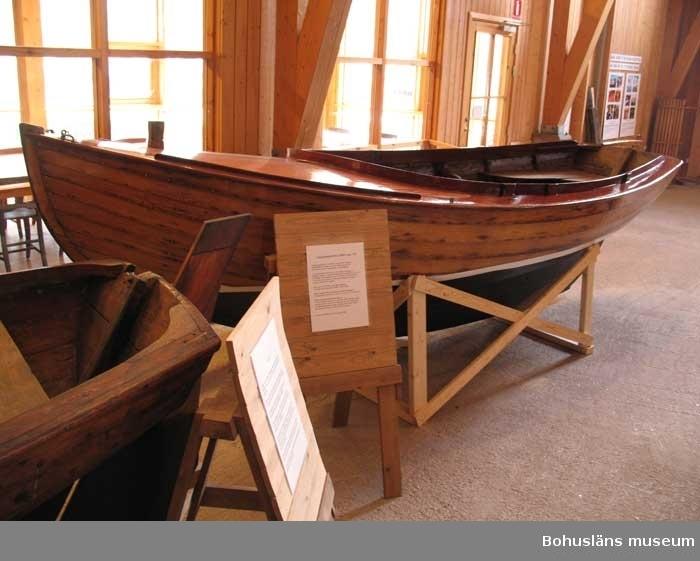 """Klinkbyggd julle, Långedragsjulle,  av typen J 10 nr. 153, """"Tio-julle"""". Längd: 5 meter, bredd: 1,90 meter, djup: 0,74 meter, järnköl: 220 kg.  Segelyta: 10 kvadratmeter. Seglet märkt J10 153. Båten är byggd på Johannes Olssons Båtbyggeri i Kungsviken på Orust 1943 och var en av sex J 10:or som byggdes där detta år. Bordläggning av ek på spant av ek, kopparnitad. Akterspegel av ek. Däck av oregonpine, skarndäck och sarg av mahogny. Pållare av ek. Roder av ek och roderkult av fur. Tofter av ek i akter, medan tofter på sidorna saknas. Fem stöd för dessa senare tofter finns kvar. Allt trä fernissat. Botten svartmålad, vit vattenlinje. Gråmålade durkar. Till båten hör originalmast samt dacronsegel från 1968."""