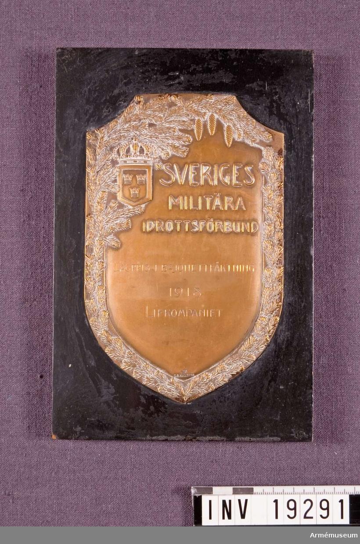 """Plakett i brons med text: """"SVERIGES MILITÄRA IDROTTSFÖRBUND LAGPRIS I BAJONETTFÄKTNING 1918 LIFKONPANIET"""". Plaketten fästad på svart lackerad träplatta."""