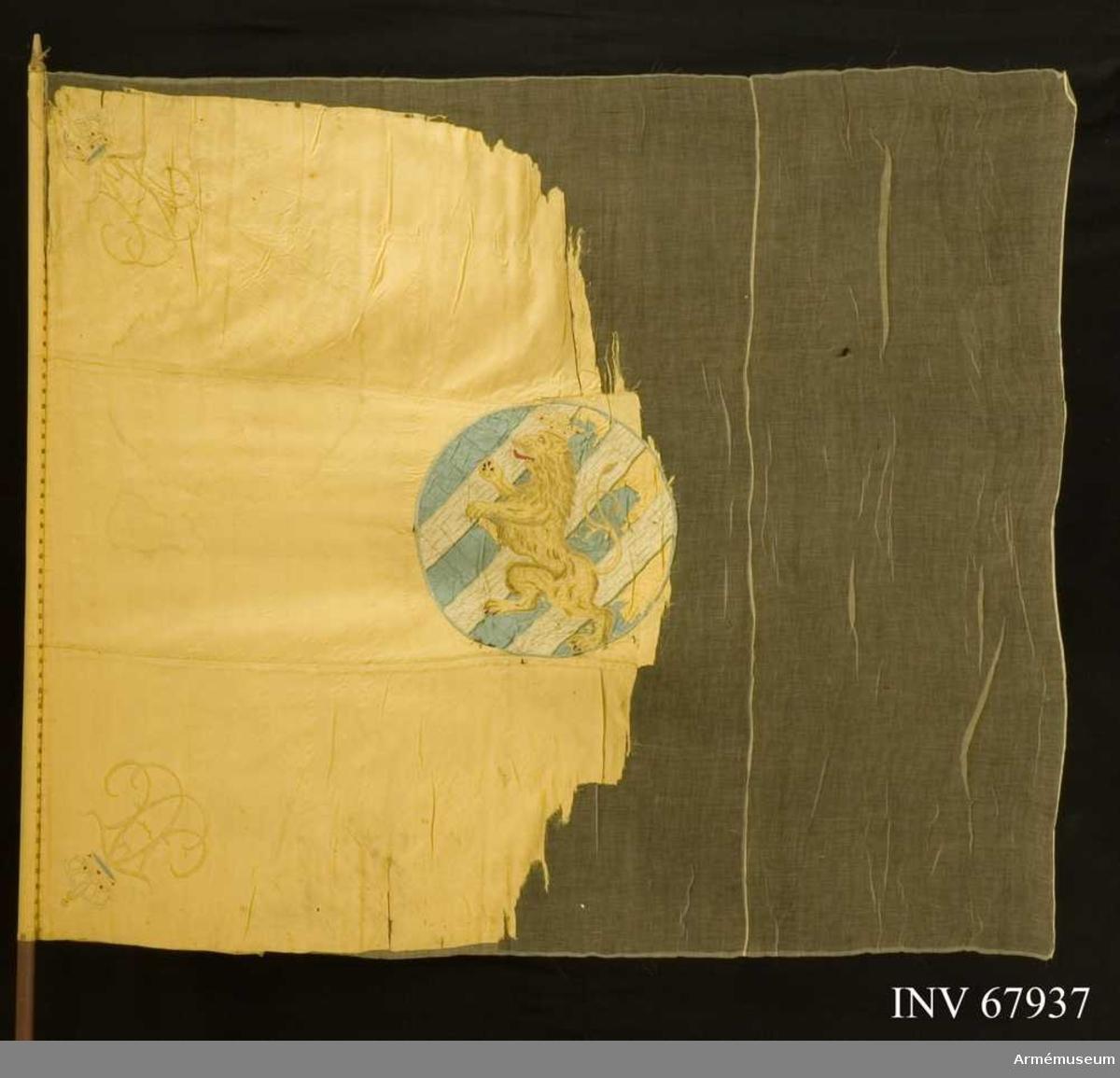 """Duk: Enkel, tillverkad av gul sidenkypert. Sydd av tre horisontella våder.   Dekor: Broderad lika på båda sidor, i mitten Göteborgs vapen: runt fält (540 x 540 mm) av blått påsytt siden varpå över tre strömmar snett från vänster i vitt siden och silke, däröver ett dubbelsvansat krönt lejon i gult siden och silke. I hörnen Adolf Fredriks namnchiffer """"A"""" med dubbelt """"F"""" under sluten krona i gult silke, kronorna med blått foder, stenar i rött, kantad med gul silkessnodd.   Duken fäst med gult silkesband och förgyllda spikar. Bandet 15 mm brett.   Stång av furu, brunmålad."""