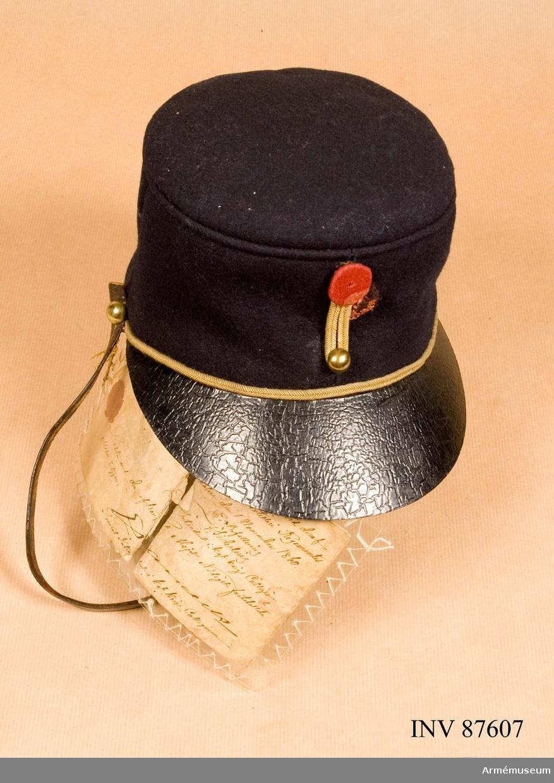 Grupp C: I.  Mössa, modelllapp 1/11 1860, g.o. 29/10 1860 (Arm. allm.) Av mörkblått käde med skärm och hakrem av läder samt försedd med gul passepoil. Rött kompanimärke. Fodrad med grått linne och vaxduk G.o. 24/10 1860 (art. allm.) modellapp 1/11 1880, av K.A.I.D. 22/3 1879.