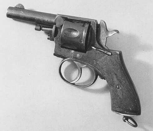 Revolver, tillverkad i Belgien, kaliber 320. Revolvern medbygel kring avtryckaren. Vapnet även utrustat med säkerhetsspärr. Påi kolvens botten är fäst en metallögla.