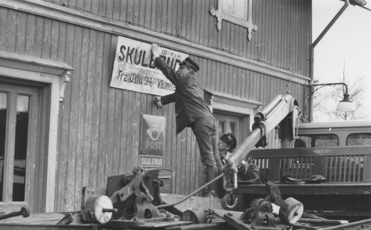 Fra Skulerud stasjon noen år etter nedleggelsen. Stasjonsskiltet demonteres for overføring til museumsbanen.