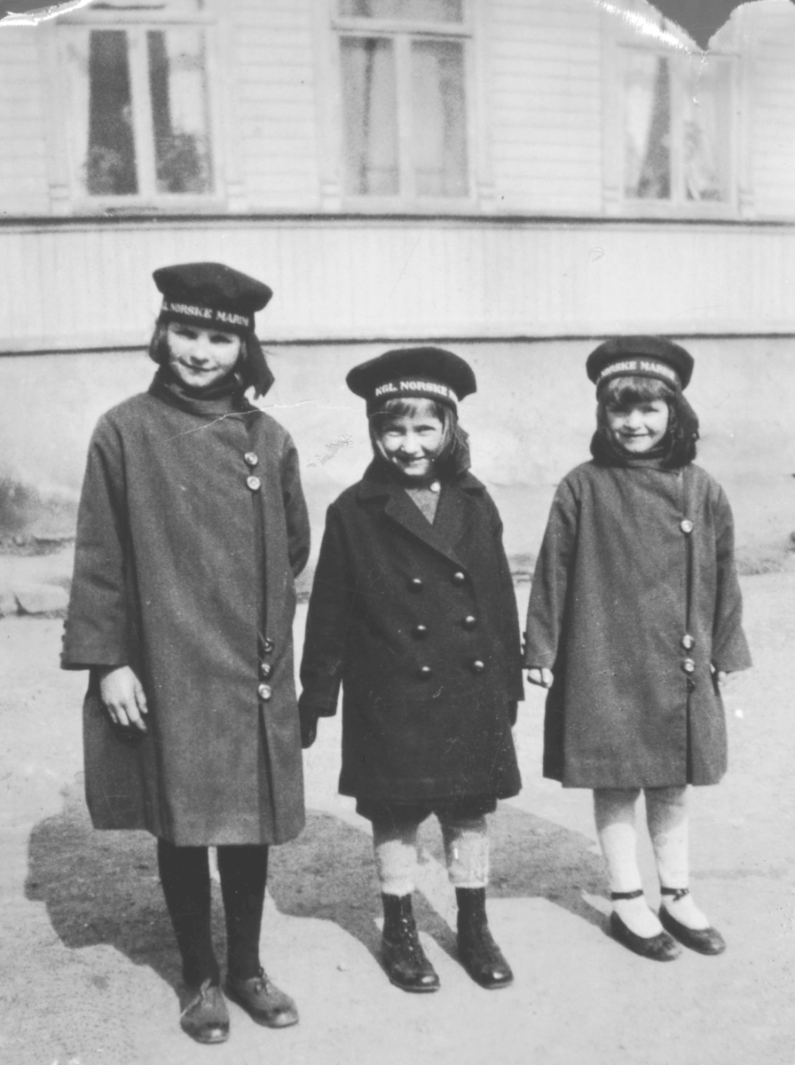 Tre jenter, kledt i kåper. På hodet har de uniformsluer med teksten 'KGL NORSKE MARINEN'. Fra venstre står: Gjertrud Evanger, Ruht Grønvigh, og Solveig Evanger. Bildet er tatt i Havnegaten. Huset i bakgrunnen er den såkalte Almestadgården vis-a-vis Evangers hus