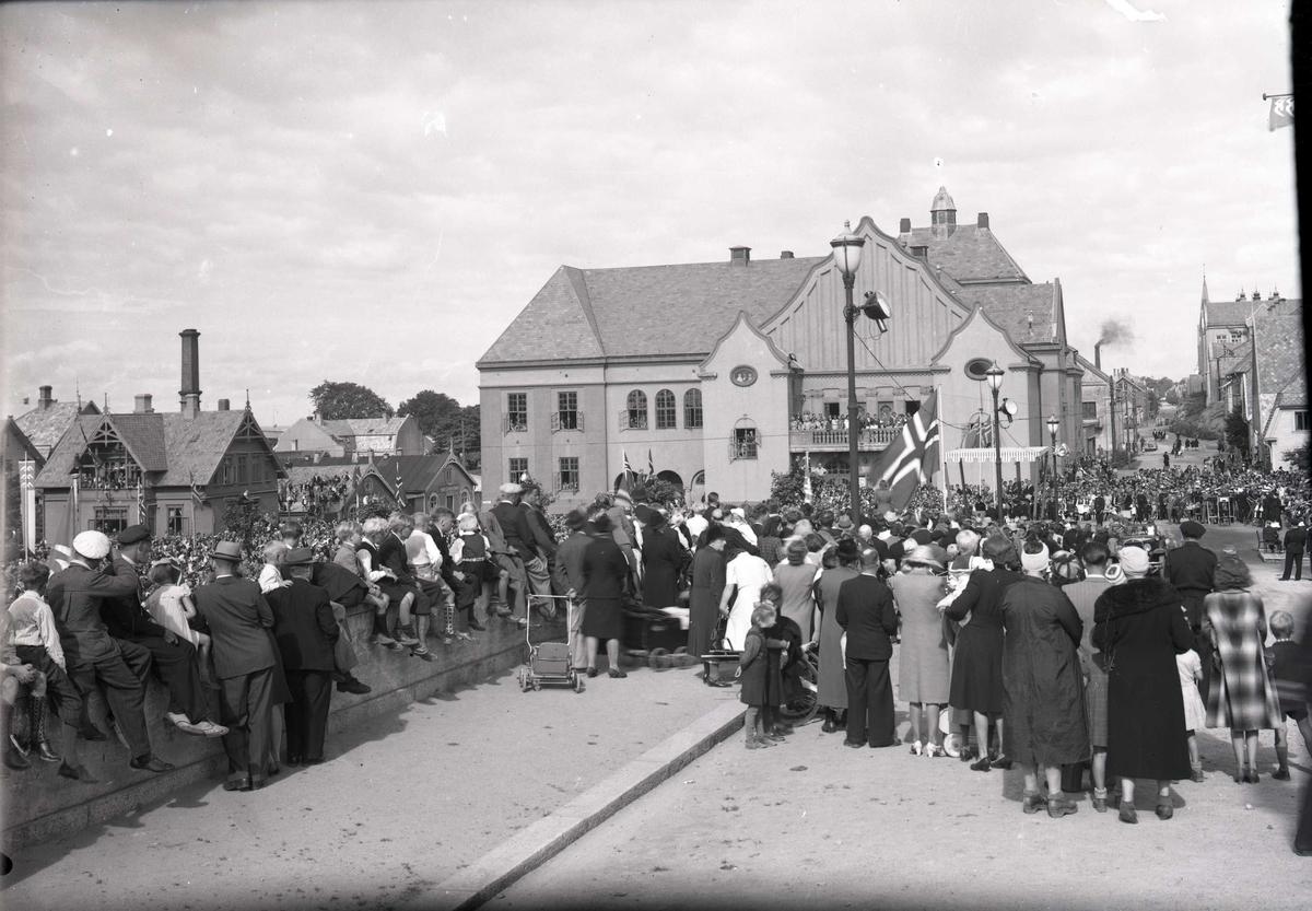 Stor folkemengde foran Rådhuset venter på kongens ankomst. Fotografert nordover Skåregt. Festiviteten midt på bildet. Fra kong Haakon VIIs besøk i Haugesund, den 22. august 1945.