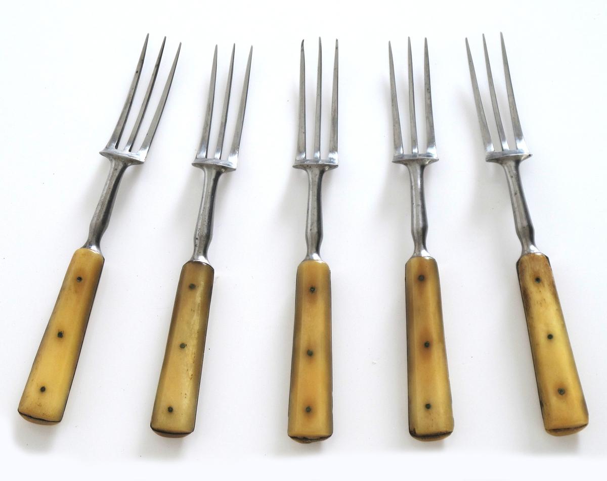 """Gafler, 11 stk. , av rustfritt stål med  benskaft. 3 tenner, fortsetter i smalt  lett profilert skaft, selve håndtaket  består av to ben-plater festet med 3 små   messing stifter. Stemplet på nedre del av  skaftet: """" STEEL  . De 11 gafler varierer  ubetydelig i største mål."""