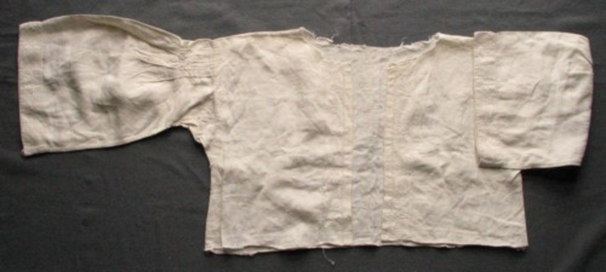 """Sommarsärk där bara överdelen är kvar, kragen och nederdelen är bortklippta. Invikt fåll (14 mm) vid de öppna framkanterna som också har broderade bårder 36 mm breda, inramade med hålsömsrader. Ärmarna korta (355 mm) och vida (230 mm), lagda veck fyra fram, fyra bak från axeln 56 mm ut, fästade med två rader efterstygn och en vågig söm med kejdesöm. På ärmslutet dubbelt tyg, samma broderade bård som vid framkanten.  Vänster ärm skarvad på ett ställe. De """"öppna"""" = vida ärmarna visar på en sommarsärk. Sidsömmar och ärmisättningen är ändrade, sydda på maskin, troligen vid senare tillfälle. Gammal märkning """"KK 11""""."""