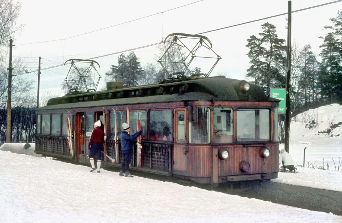 A/S Holmenkolbanen. Sognsvannsbanen. Vogn 205, type 1934 (Skabo, Westinghouse). Reisende løsner ski fra skistativ.