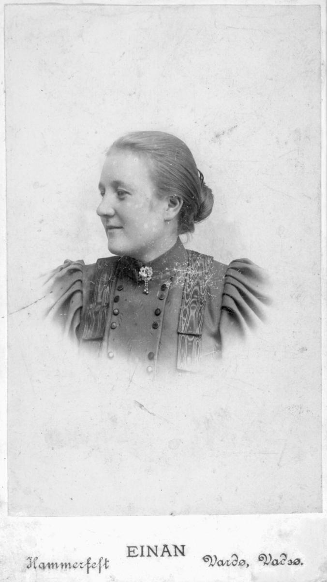 Et portrett av en ung kvinne, muligens Emma Kristina Wickstøm. Bak bildet står det skrevet 'Amelie'. Hun er kledd i en dekorativ overdel, med en brosje på halsen.