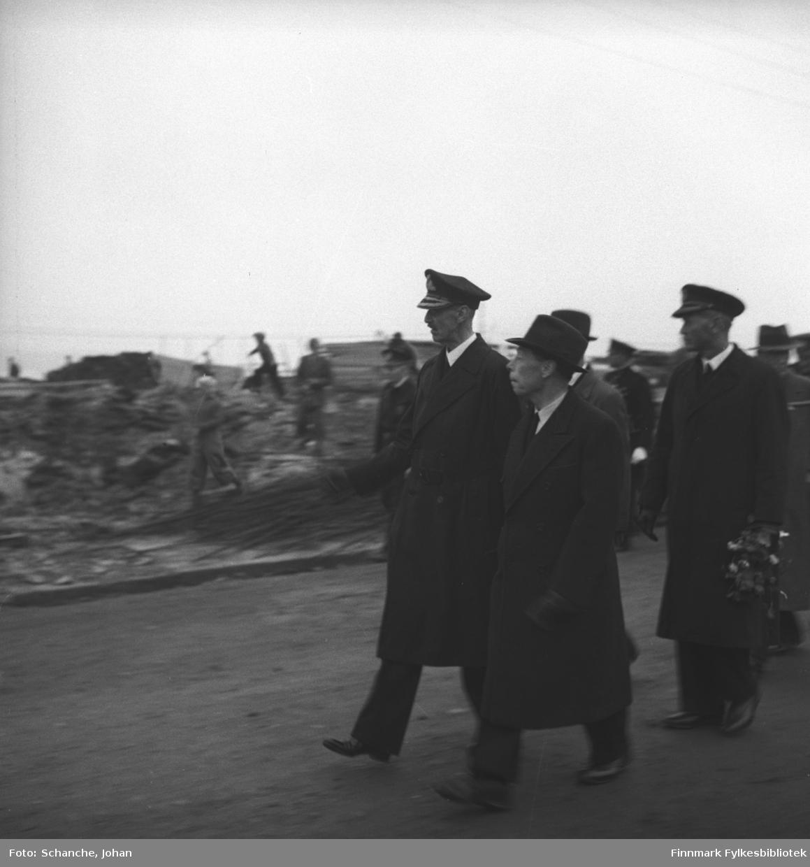 Kongebesøk: Kong Haakon VII, fylkesmann Hans Gabrielsen og kongens adjutant kommandørkaptein Bruusgaard går langs gata i Vadsø.  Noen unger springer på / bland ruinene ved veikanten.