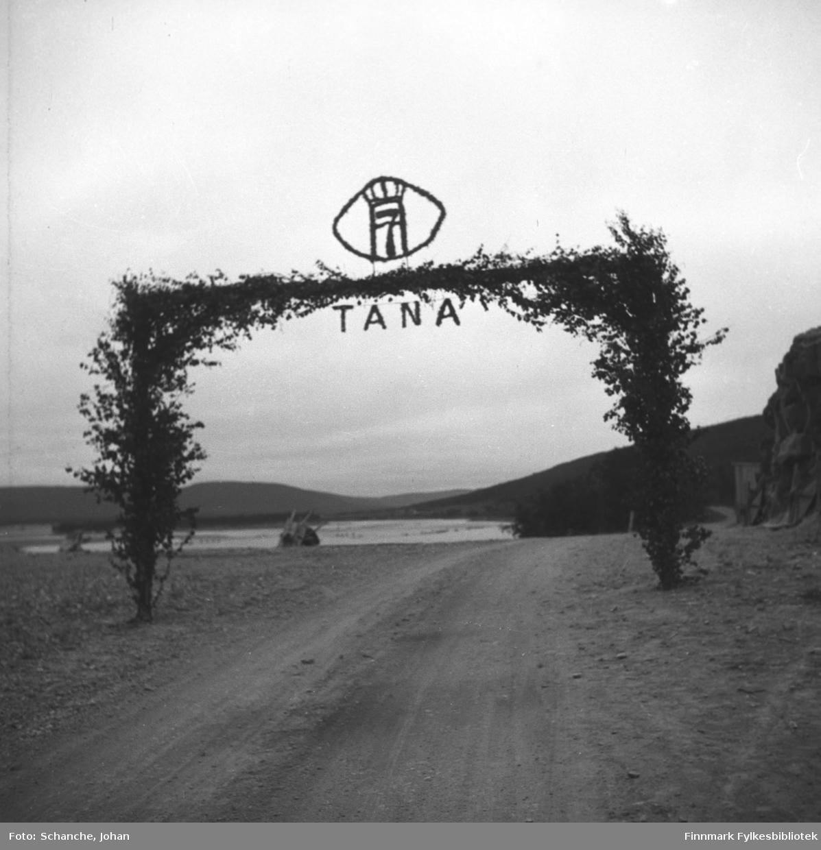 Kongebesøk:  Kong Haakon VII besøker Tana. Kongen reiste fra Vadsø og stoppet i Vestre Jakobselv, Nyborgmoen, Skippagurra og Langnes der han spiste aftens- laks og rabarbargrøt. På bildet granporten over veien i Tana. Overst på porten står ordet TANA og Tanas våpen. Tanaelva skimtes bak porten.