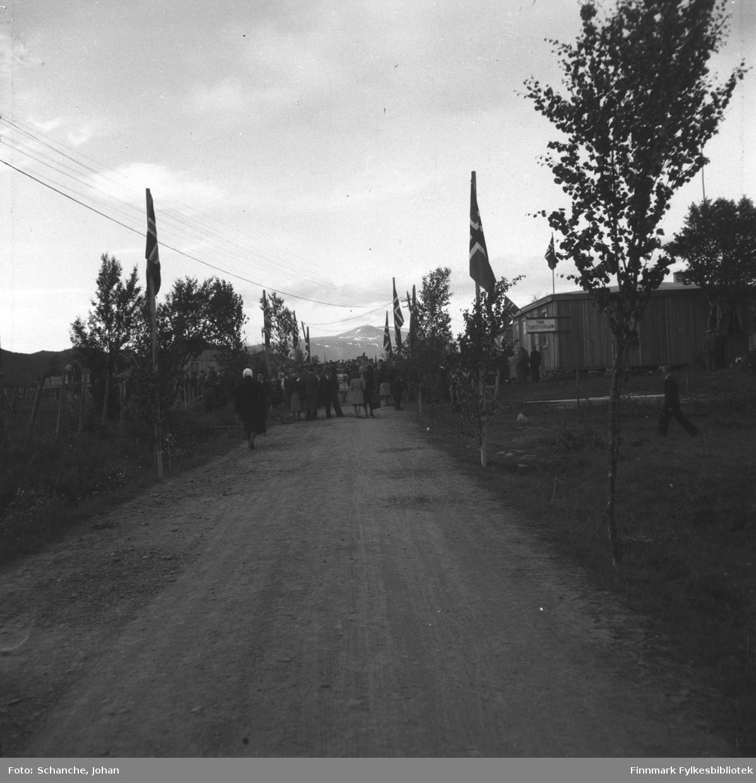 Kongebesøk i 1946:  Kong Haakon VII besøker Tana. Grusvei  mot Tana Turiststasjon. På begge sider av veien står faggestanger.  Folk står lengre bort på gata foran hotellbrakken og venter på Konges ankomst.