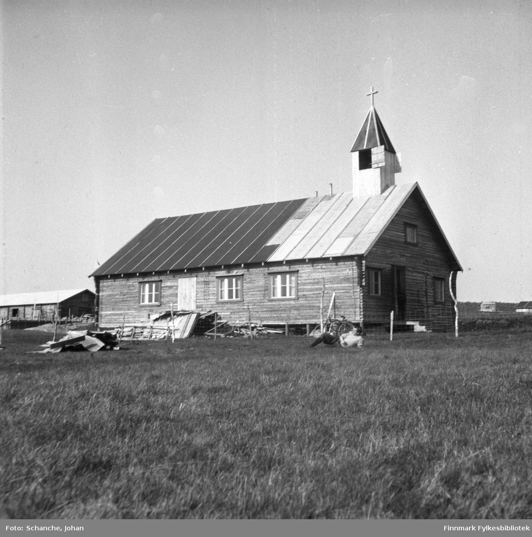 Et bilde fra kirken i Kautokeino. En mann ligger på gresset og koser seg i sola foran kirken. Ved siden av ligger byggematerialer, taket på kirken er under reparasjon