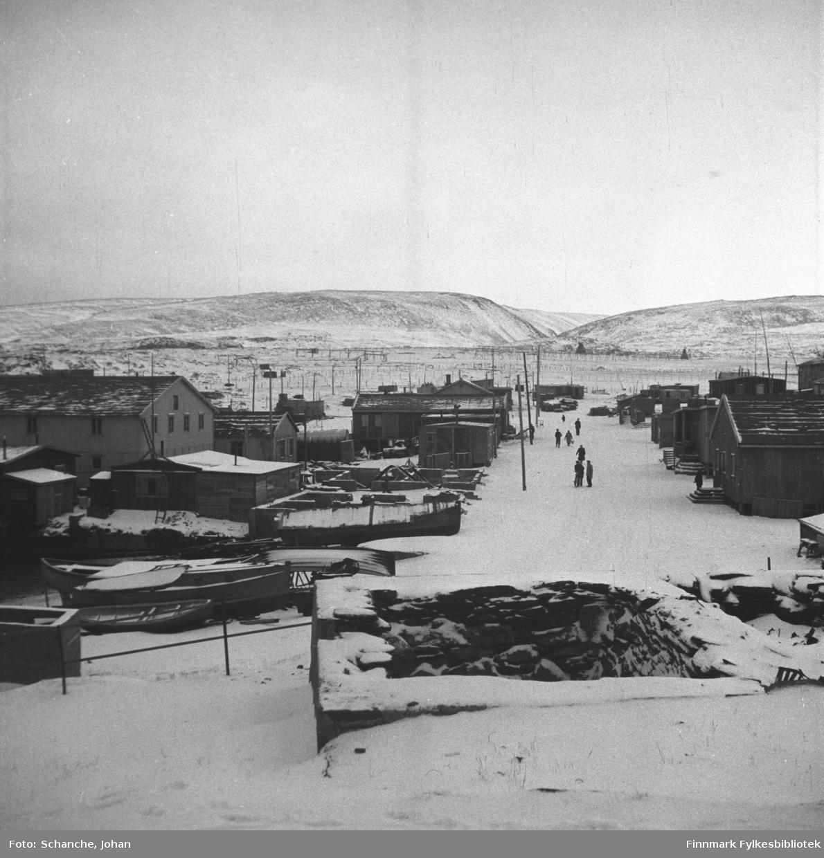 Oversiktsbilde fra Berlevåg i gjenreisningstid. Foran på bildet ruiner,  gate, noen mennesker på gata.  På begge sider av gaten står det byggninger, ruiner og boliger under bygging.