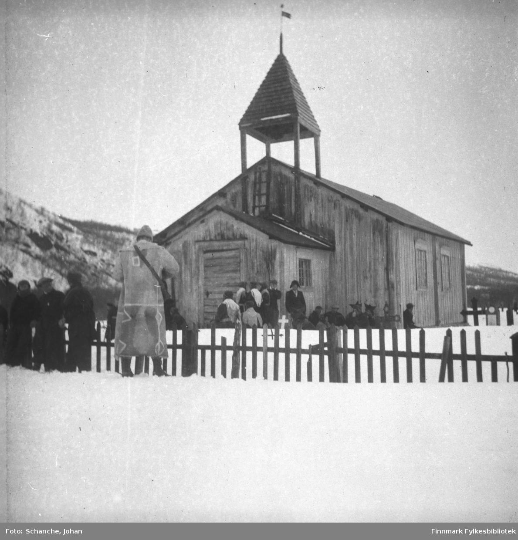Polmak kirke fotografert på påsken -46. Mennesker, en del av dem i samedrakt, venter (på brudeparet, dette er trolig en vielse) utenfor kirken. En mann i en lang skinnjakke står ved siden av kirkegjerden og fotograferer?.