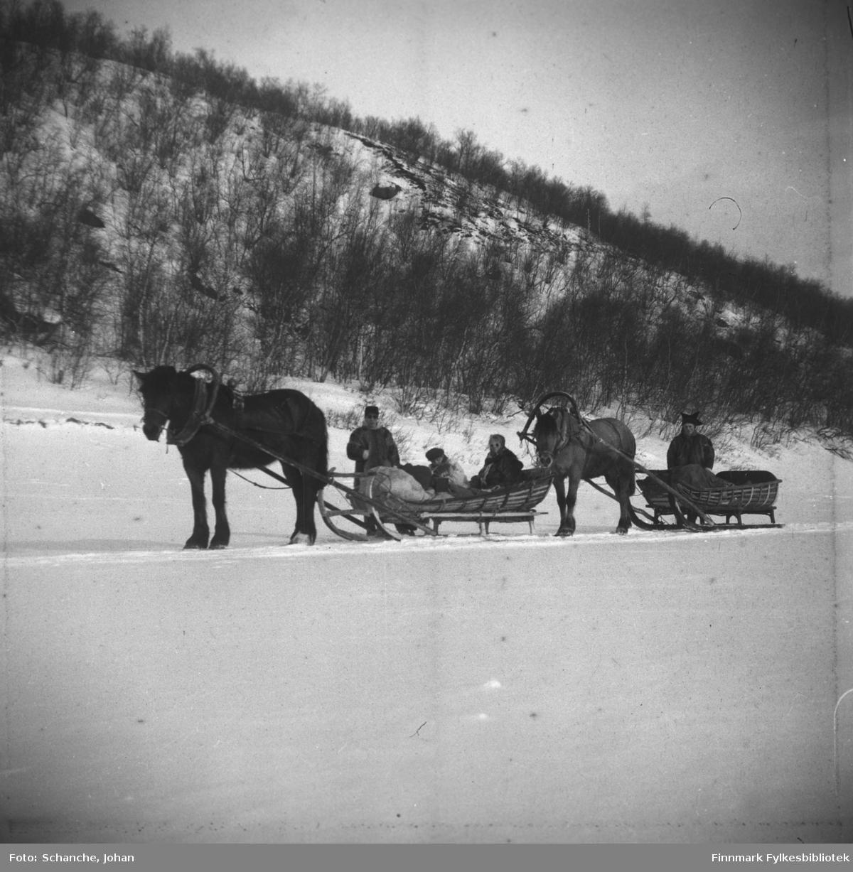 To mennn og to kvinner kjører to hester med sleder på isen over Tanaelva påsken -48. Sledene ble kalt styrslede og var spesielt laget for turkjøring og har seletøy med en bue/bøyle over ryggen på hesten. Hesten hadde også en bjelle som stod på hesteryggen, kalt Sedolk, muligens av finsk opprinnelse. Den ene av mennene er kledd i sameklær / pesk og står ved siden av sleden. På den andre sleden sitter to kvinner.  Landskapet er dekt av snø.