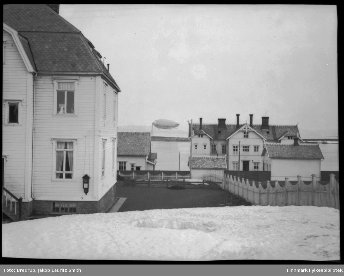 Luftskip ankret opp ved luftskipsmasta på Vadsøya, mai 1926 eller 1928. Bildet er tatt mellom Statens kysthospital (nærmest fotografen til venstre) og Fylkessykehuset i Vadsø til høyre.  Mellom bygningene ser man gjerder og uthus. Er dette luftskipet Norge eller Italia?  Når man forstørrer bildet, kan det se ut som om det er Italia, men teksten er svært utvisket.  Det ligger mye snø igjen i hagene, og det var mye snø fortsatt i mai 1926 da Norge kom til Vadsø.  Usikkert. Bilet har denne teksten i Vadsø-kalenderen 1999: Byens sykehus lå samlet i Hvistendahls gate.  Kysthospitalet, som stikker fram til venstre, offisielt kalt Skrufulosehospitalet, ble bygd i 1918, men ble byens sykehus noen år etter krigen.  Til høyre nedenfor gata Sykehuset, bygd i 1898, men som ble bombet og brent 23. august 1944.  Mellom disse bygningene sees Lasarettet, som var et eget isolat for epidemier, ferdig i 1913, da spanskesyken herjet.  Lasarettet ble også brukt som isolat ved skarlagensfeber og difteri.