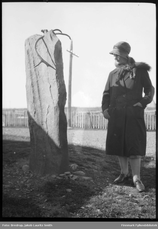 Hildur Norvik kledd i hatt og kåpe med revepels, betrakter Ivarsteinen på Sletten i Vadsø. Steinen har antakelig opprinnelig vært en samisk offerstein.