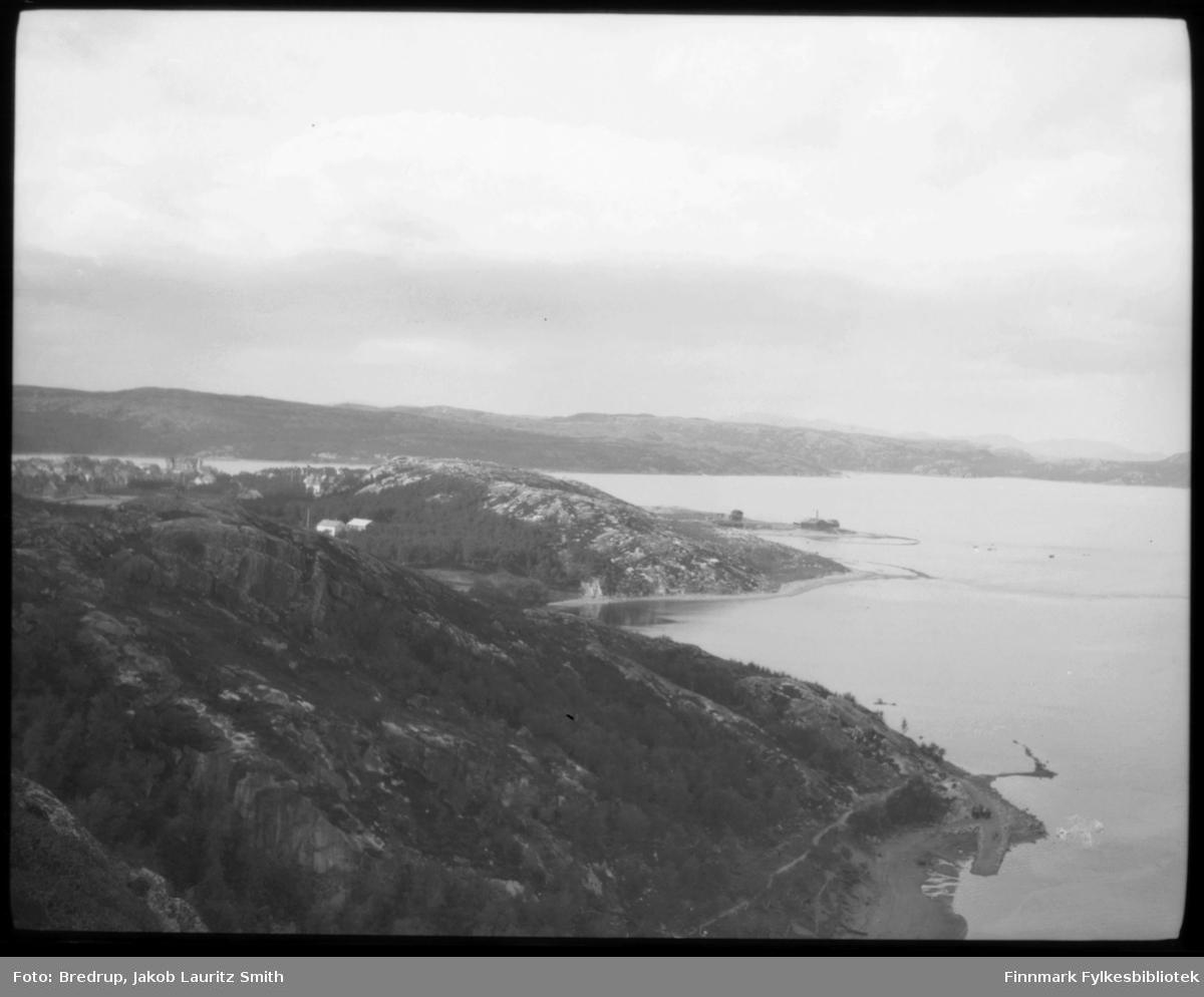Oversiktsbilde av Kirkenes, tatt fra en høyde over byen, ganske langt unna.  Midt i bildet skimter vi folkeskolen, og man kan også se litt av øvrig bebyggelse..  I bakgrunnen Bøkfjorden og fjellene.