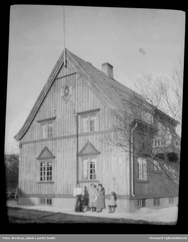 Familie fotografert utenfor et staselig bolighus i Kirkenes. Funksjonærbolig? Bildet kan også være tatt i Bjørnvatn.