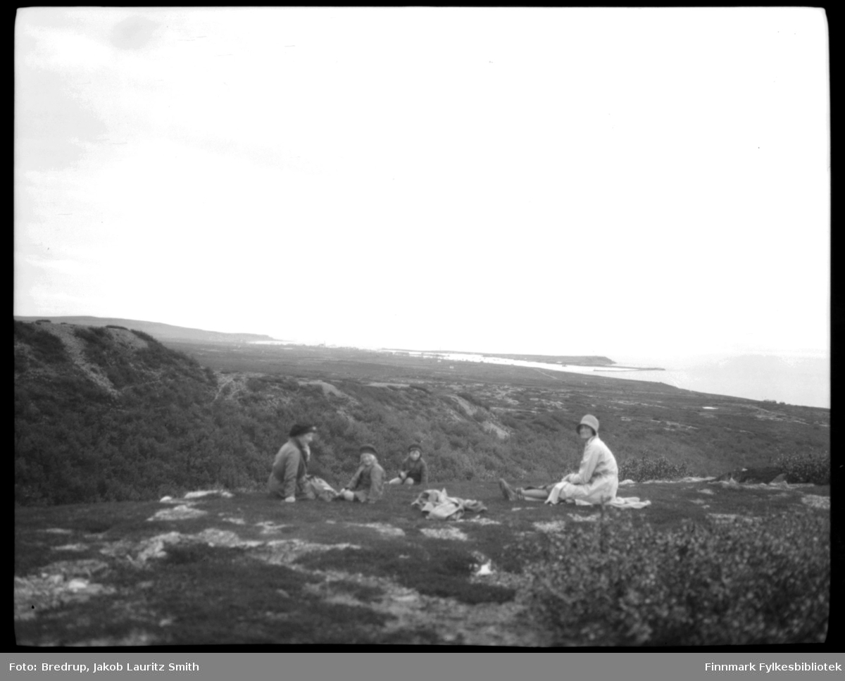 To kvinner og to barn på tur. På bildet sitter de og hviler.  I bakgrunnen ser vi bebyggelsen i Vadsø og Vadsøya.