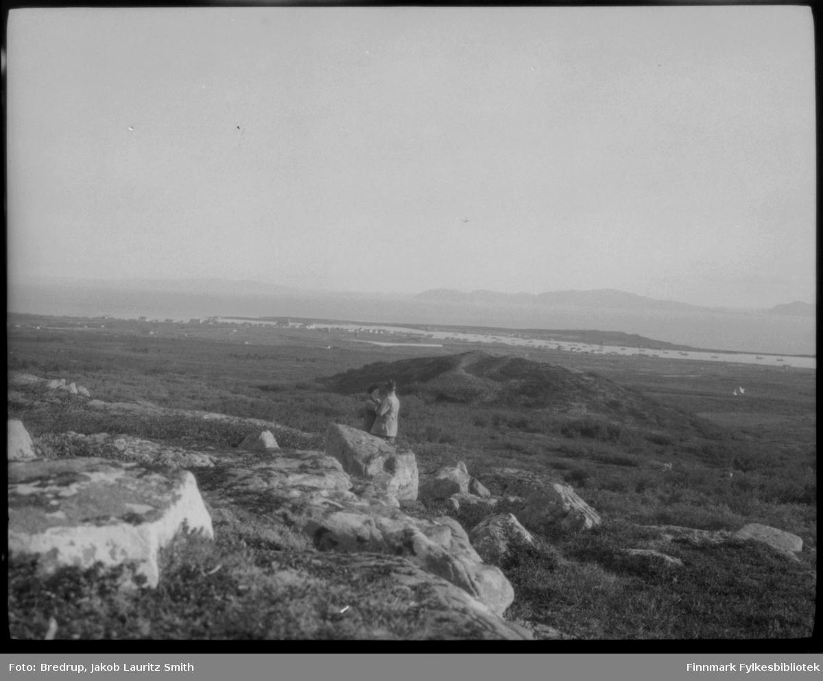 Et ektepar, Hildur og Jakob Bredrup, står og holder omkring hverandre i landskapet over Vadsø.  I bakgrunnen er det fin utsikt over bybebyggelsen og Vadsøya, fjorden.