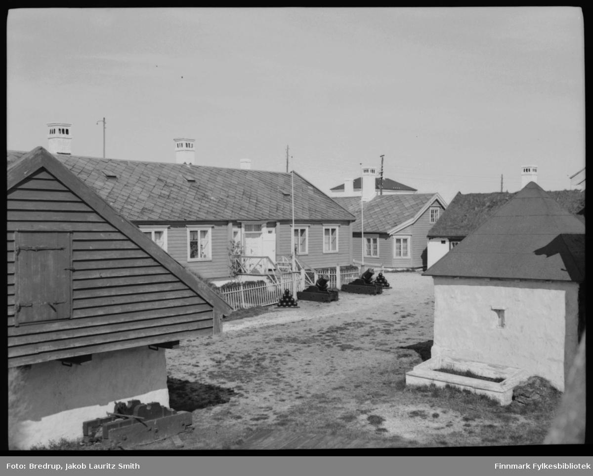 Flere bygninger på Vardøhus festning.  Midt i bildet kommandantboligen med den berømte rogna som pakkes inn hver høst.  Til høyre i bildet aggregathuset, som opprinnelig var en brønn.  Forskjellige andre bygninger på festningsområdet.