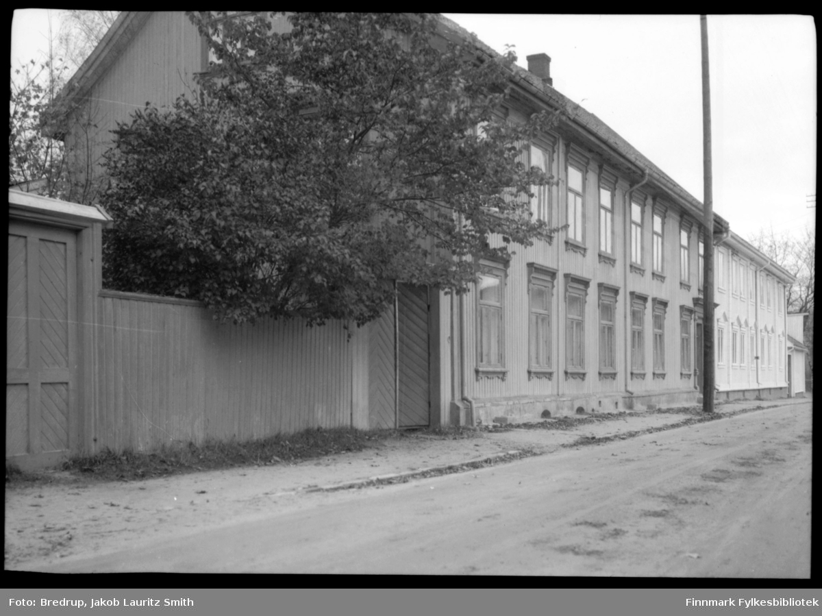 En bygate i Vadsø.  Et høyt og skjermende gjerde foran en hage, et flott tre henger over gjerdet og mot gata.  Vi ser to bolighus bygget sammen til en sammenhengende rekke.