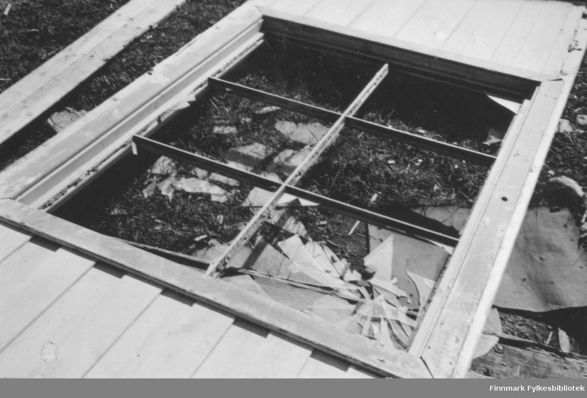 Nærbilde av et vindu som er innebygd i en del av en vegg. Veggdelen ligger på bakken, og vinduet er knust