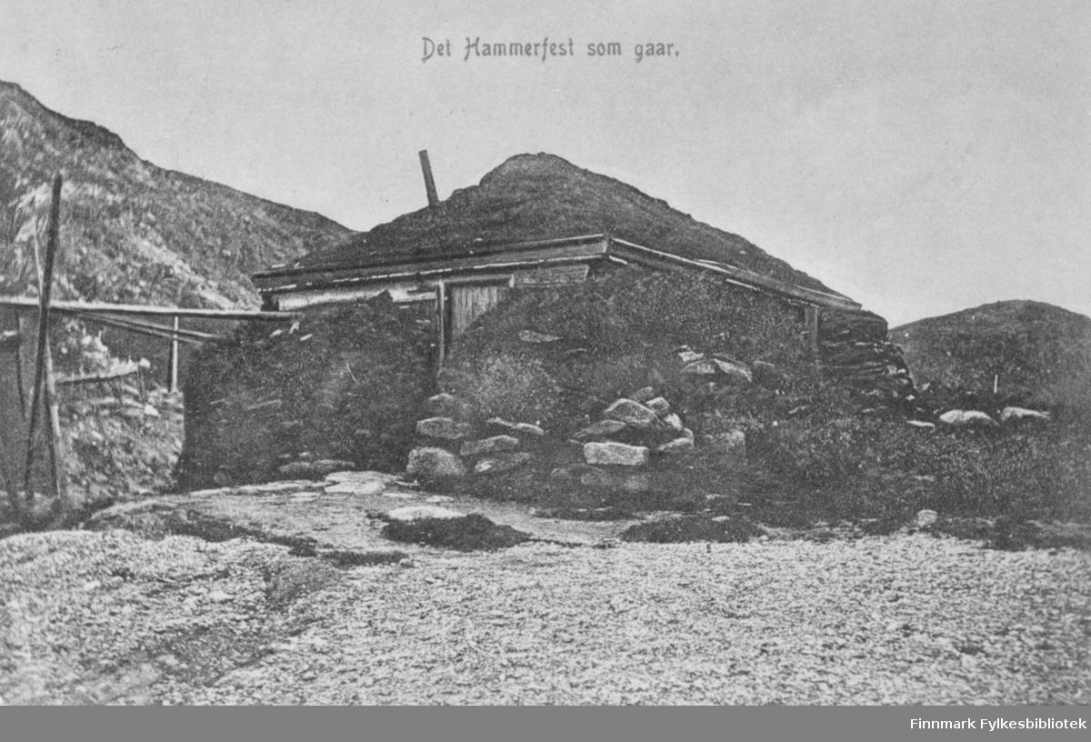 Postkort med trykt tekst 'Det Hammerfest som gaar' - motivet en trehytte isolert av oppstablet torv langs ytterveggene