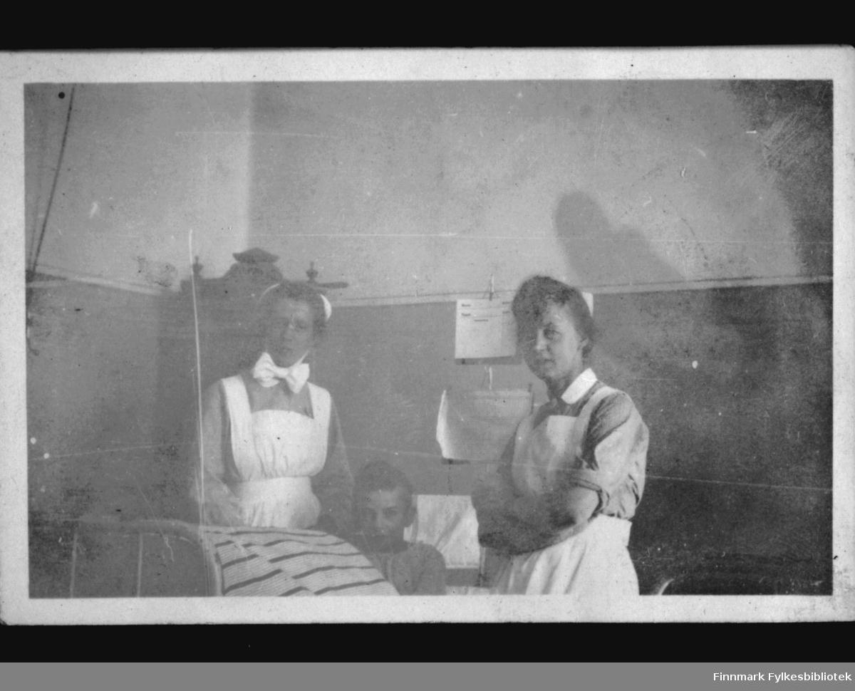 To sykepleiere fotografert ved senga til en ung pasient
