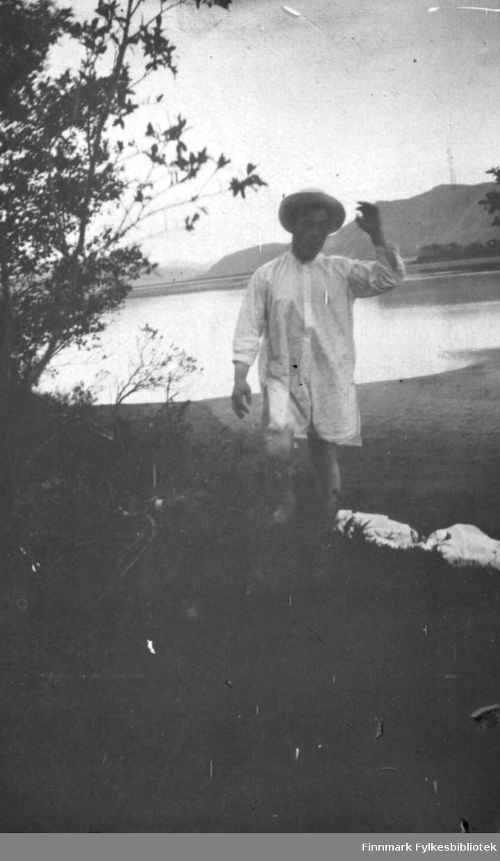 Hans Gabrielsen nyter sommeren, kun iført skjorte og hatt. Han har kanskje badet? I bakgrunnen sandstrand ved Tanaelva, kanskje bilde er tatt i Boftsa siden vi ser litt av Norskholmen helt til høyre. I bakgrunnen på østsida ser vi Rødberget, Blåberget og Storfjellet mot Austertana. Eller det kan være sett fra Ruostefielbma og Harrelv - Harrholmen på motsatt side i høyrekant. I 1916 bestyrte Gabrielsen sakførerforretningen til Hagbarth Lund, som var valgt inn på Stortinget