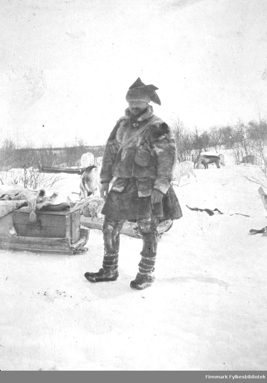 En mann, John Varsi, er fotografert ute i snøen. Han er kledt i pesk, stjernelue og skaller. I bakgrunnen er det reinsdyr og flere pulker.