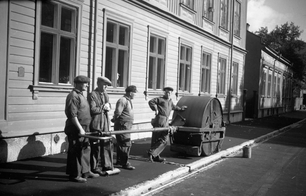 Kommunalarbetare asfalterar en trottoar i Jönköping på Gjuterigatan 20. Från vänster: Rune Åsberg (kommunalarbetarförbundets ordförande) (2), Torsson (3), Torssons son (4).