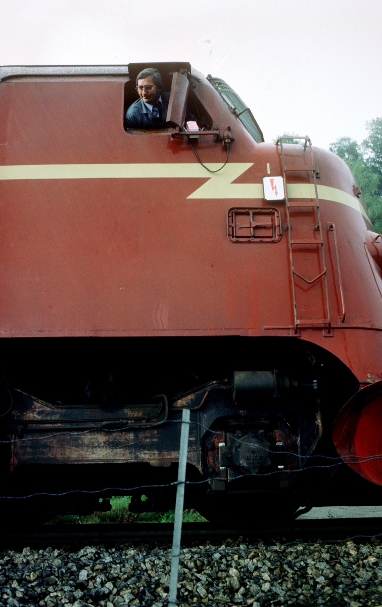 Lokomotivfører Åge Hoff på NSB dieselelektrisk lokomotiv Di 3 611 i godstog 5793 (Trondheim - Bodø) venter på kjørsignal i Østborg blokkpost. Melkekartongen er plassert på sin faste plass for kjøling.