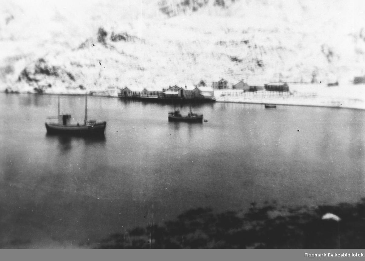 Et bilde fra Tyfjord. To båter ligger på fjorden, bak dem fiskannlegg og noen bolighus. Landskapet er dekt av snø.   Bildet er uskarp.