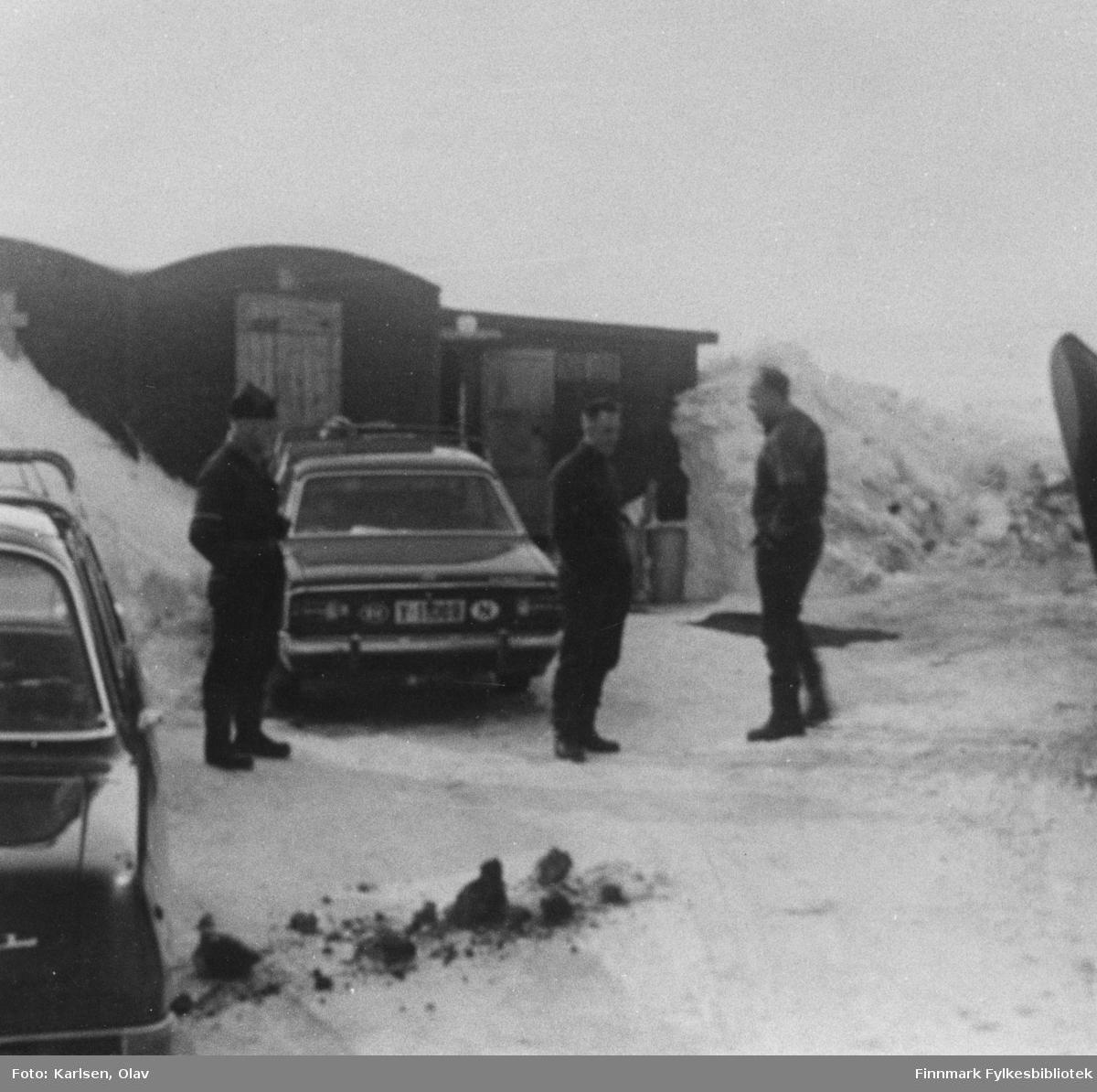 Skallelv brøytestasjon. Fra venstre: Almar Forsberg, ukjent og Erling Kvam. I bakgrunnen ser man noen brakker. På bildet er det også noen biler