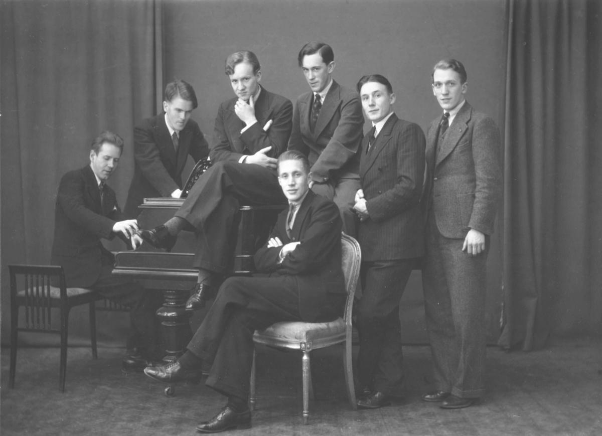 Et gruppebilde fra musikanter, fra venstre: Godtfred Pedersen sitter ved flygel, Mangne Elvestrand, Åsmund Holt, Ole Skjerven, Trygve Bræin, Magnus Landro og sittende på stolen Leif Svelberg. Bildet er tatt i Oslo hos fotograf Eivind Enger.