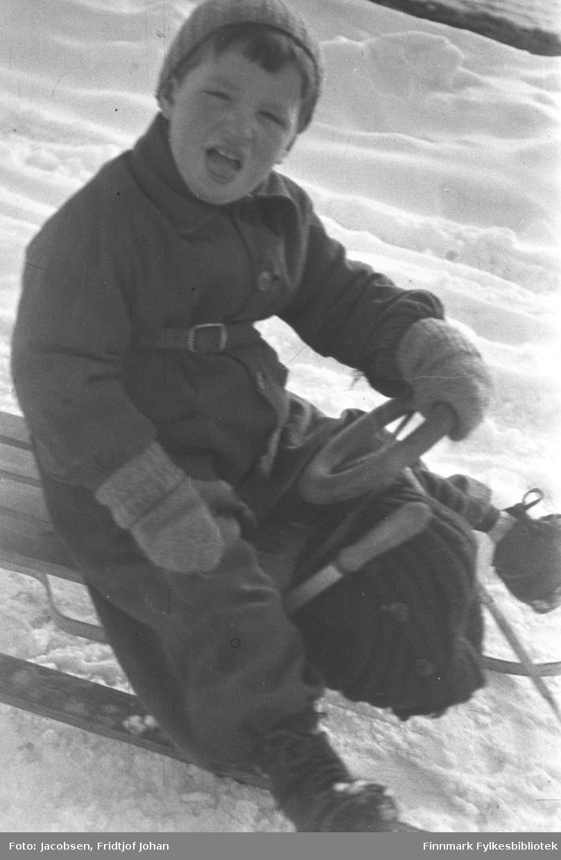 Gutten på bildet heter Sigurd Logn og var en lekekamerat av Arne Jacobsen.  Han sitter på en rattkjelke  iført en ganske mørk buksedress og litt lysere lue og votter.