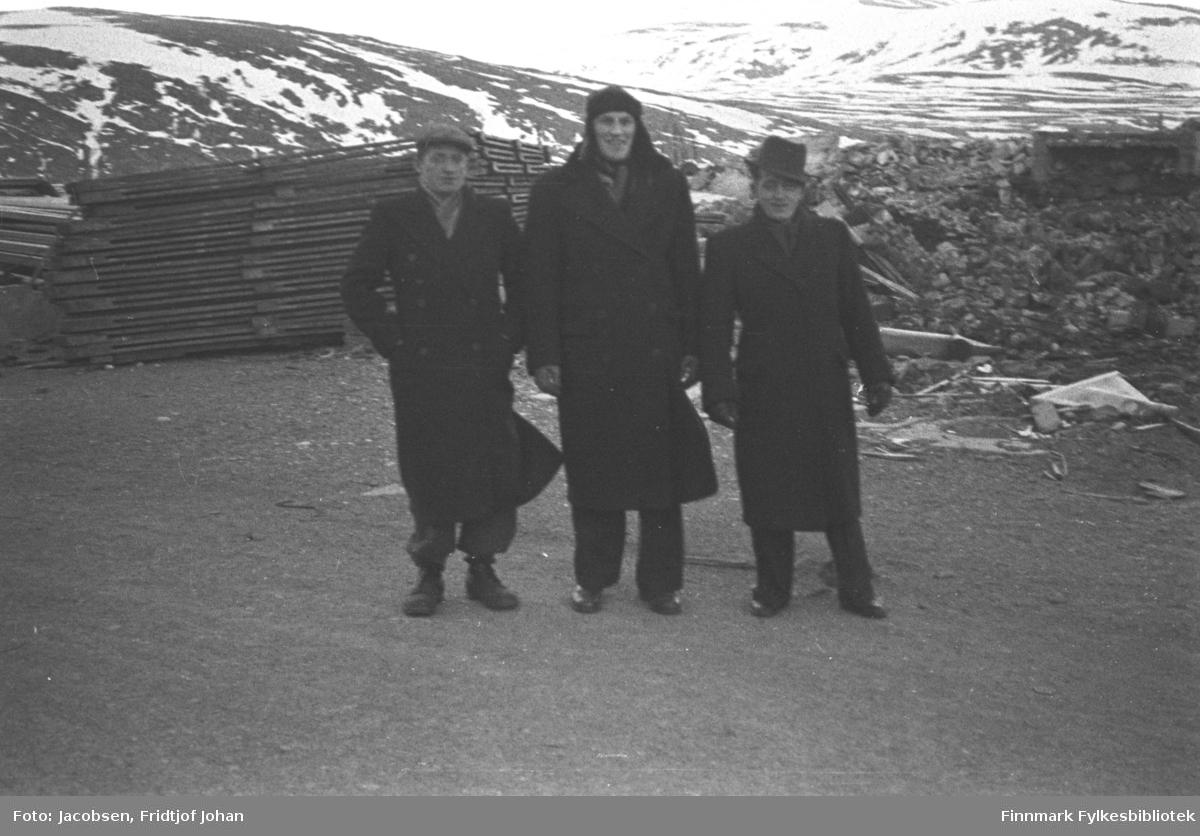 Tre menn, alle i mørke frakker, bukser og sko, poserer for fotografen. Til venstre på bildet står Reidar Hansen. Han har en ganske lys six-pence på hodet. I midten står Audun Iversen som har en skinnlue på hodet. Til høyre på bildet står Johan Olsen med en hatt på snei. Plassen der de står er snøfri og ganske flat med grus-/jorddekke. Bak dem, til høyre på bildet ligger hauger med rester og skrot fra raserte bygninger. Til venstre på bildet ligger store stabler med plater som ble brukt til å bygge brakker/hus med. Fjellene i bakgrunnen er Fuglenesfjell til venstre på bildet, som går ned mot Fugelnesdalen. Oppe til høyre på bildet står Storfjellet. En del snø ligger i terrenget, men en del bare flekker ses også. Bildet er speilvendt!