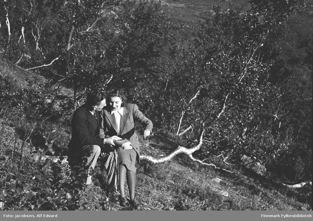 Ragnvald og Alfhild Marie Jacobsen i Jansvannskogen utenfor Hammerfest, sommeren 1947. Alfhild sitter på en grein. Hun har en ganske lyst skjørt på seg og jakke i samme farge. Under har hun en hvit bluse med store snipper og på beina har hun mørke sko. Ragnvald sitter på samme greina. Han har lys bukse og mørk dressjakke. I halsen ses en liten flik av den lyse skjorta og et mørkt, stripete slips. Bakken skrår ganske mye der de sitter og det er endel gress i området. Mye løvtrær og busker i terrenget rundt dem. Sola skinner og det ser ut til å være en flott sommerdag.